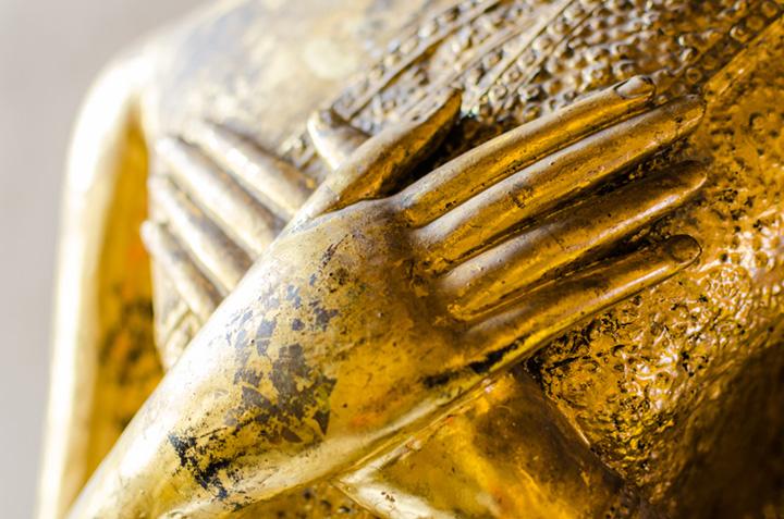 Goldene Buddhastatue mit auf der Brust ruhenden Haenden