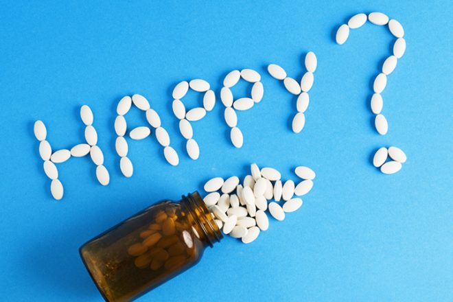 "Word ""happy"" written whith pills on blue background. The photo is to convey a concept of excess medicines in modern life"