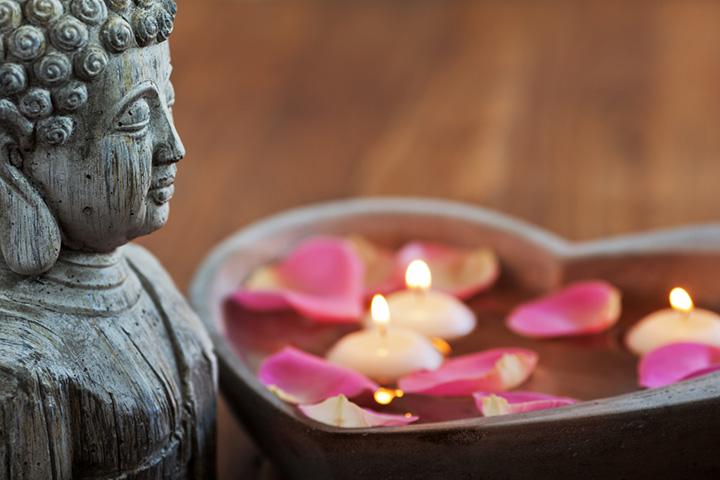 Buddhafigur neben einer herzförmigen Steinschale gefüllt mit Wasser, Rosenblüten und schwimmenden Kerzen