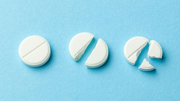 »Weiße Tabletten auf blauem Hintergrund. Wenige Tabletten zerbrochen in der Hälfte, wodurch die Dosis des Arzneimittels reduziert wurde.«